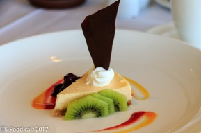 House made Cheese cake with Kiwi and blackberry coulis, topped with dollop of fresh whipped cream and rich chocolate